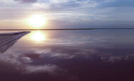 Beautiful sunrise over a pink lake near a small island, the reflection of the blue sky on the water, the purple color of the seascape.