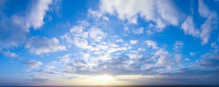 Panorama of bright evening and morning sky, shining sun.