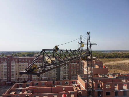 Aerial view of cargo crane boom high in the sky.