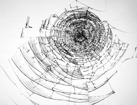 Cracked glass from impact, broken protective glass of the phone on a white background. Texture for design.