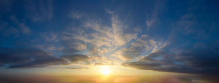 Sunset sky panorama with clouds and orange glow. 免版税图像