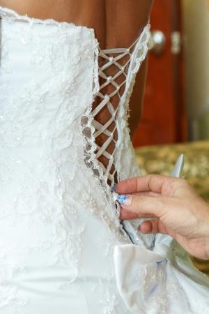 mother  tighten the corset wedding dress  daughter  photo