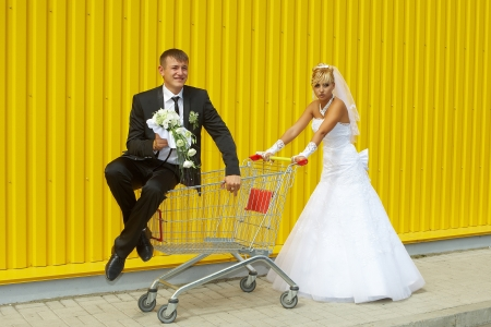 funny bride and groom playing with a basket of supermarket photo