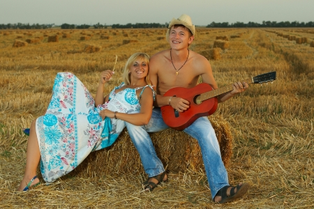 A  fun  pair of lovers on hay with guitar in summer at sunset  photo