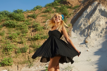 whirling: Happy blonde girl in nature in black dress whirling dancing Stock Photo