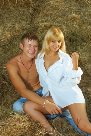 hayloft: Happy smiling seductive couple  half-clothed in the hay Stock Photo