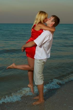 pareja apasionada: hombres y mujeres apasionados besan en la playa del mar la puesta del sol