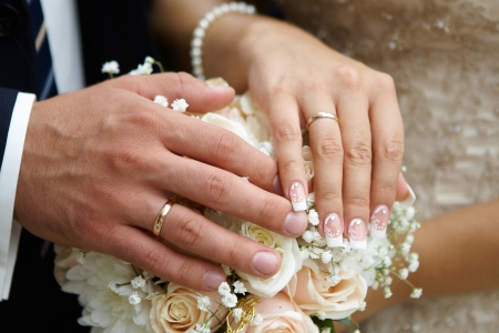 Hands of the groom and the bride on wedding flowers