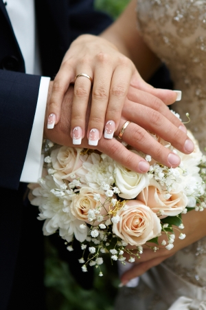 Hands of the groom and the bride on wedding flowers photo