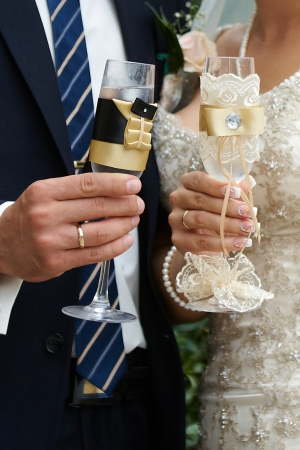 wedding glasses in hands of the bride and groom, wedding rings photo