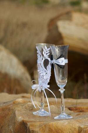 Two wedding glasses on a brown stone background in the image of the bride and groom photo