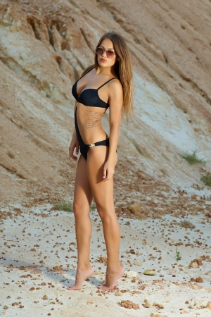 Beautiful girl with perfect figure in a bathing suit and sunglasses photo