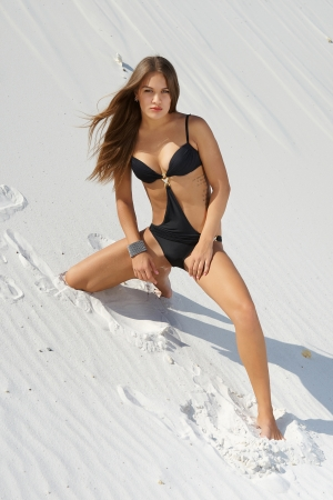Beautiful girl with perfect figure in a bathing suit background  on white sand photo