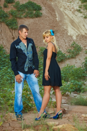 Couple in black and blue clothes outdoors talk offended photo