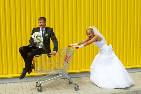 funny bride and groom playing with a basket of supermarket Stock Photo