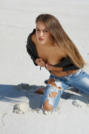 ripped jeans: Tanned beautiful girl in jeans and a leather jacket in the desert Stock Photo