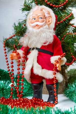 Pictures of Toy Santa Claus near Christmas Tree photo