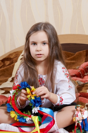 Adorable Little Girl Sitting Cross Legged with a bright wreath photo