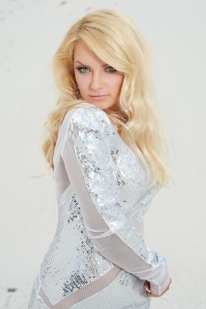 arena blanca: chica elegante con un vestido blanco brillante en la arena blanca