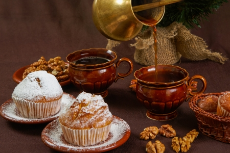 Fresh muffins on a brown table with a cups of coffee and coffee pot photo