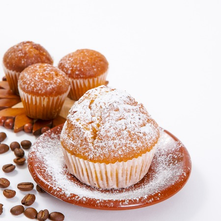 Fresh muffins with powdered sugar and coffee beans on a white background Stock Photo