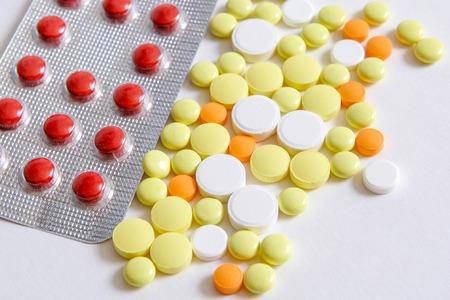 pilule: Pillole mucchio giallo arancio rosso bianco su sfondo bianco