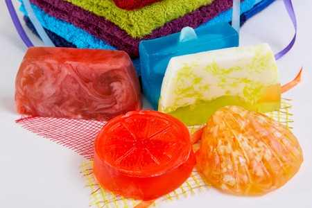 colorful towels with  handmade soap on a white background photo