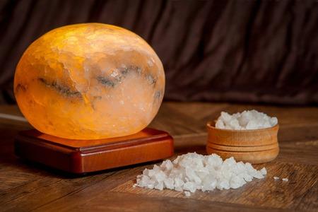 salt lamp: Healthy sea salt and salt lamp on wooden bowl closeup