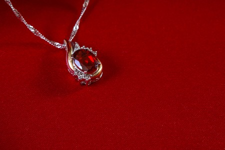 red  stone: jewelery luxury ruby pendant on a red silk