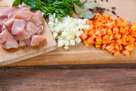 raw chicken meat on cutting board with vegetables and spices photo