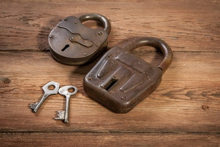 Key and rusty lock on vintage wooden background photo