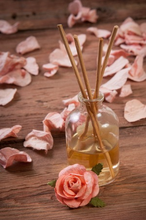 Fragrance sticks or Scent diffuser with rose flowers on wooden background Stock Photo