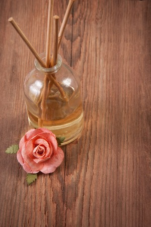 scent: Fragrance sticks or Scent diffuser with rose flowers on wooden background Stock Photo