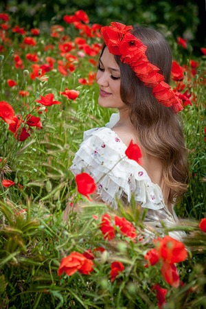 Lovely happy brunette female, sitting in the poppy flower photo
