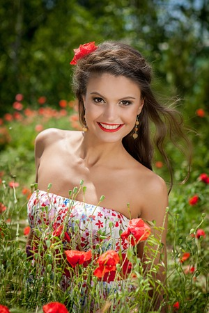 Lovely happy female closeup portrait, sitting in the poppy flower          photo