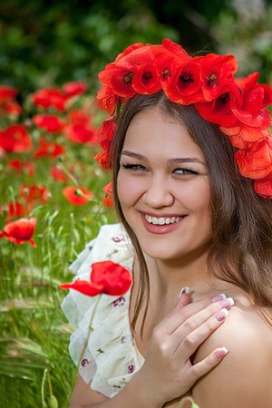 Lovely woman closeup portrait, sitting in the poppy flower          photo