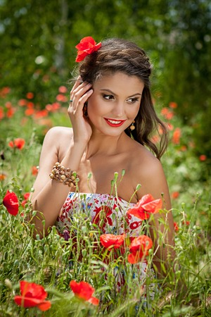 Lovely sexy woman closeup portrait, sitting in the poppy flower          photo
