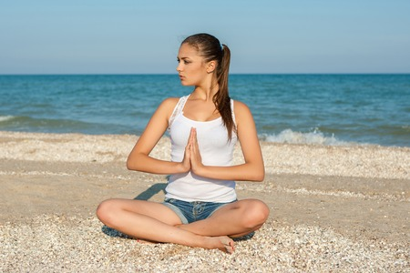 Caucasian young woman practicing yoga or fitness at seashore at sunset photo