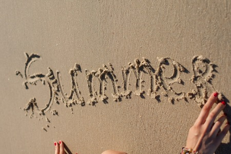 suntanning: girls hand makes the inscription on the sand Summer