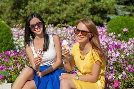 Happy young beautiful women friends eating ice cream photo