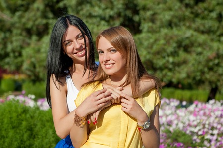 Beauties in style. Two beautiful young well-dressed women smiling at camera while standing embracing outdoors photo