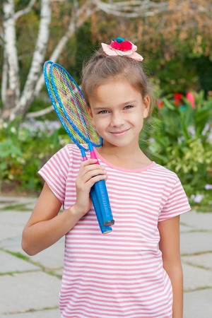 Cute 8 years old girl with racket Outdoors photo