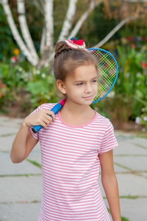 8 years old: Cute 8 years old girl with racket Outdoors