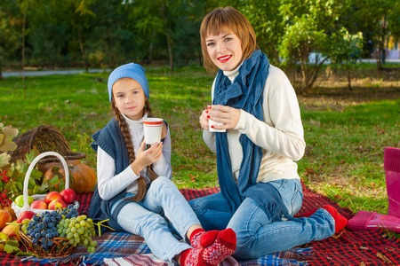beautiful happy mother and daughter sitting on a picnic. With a cup of hot tea. Autumn harvest. Apples, pumpkins, grapes, viburnum. photo