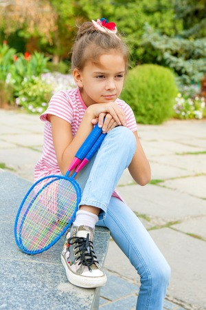 8 9 years: Sad pensive cute 8 years old girl with racket outdoors. Looking away. Stock Photo