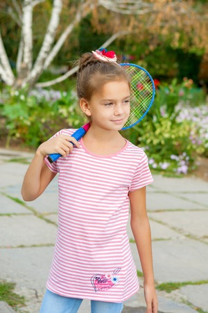 8 years: Cute 8 years old girl with racket Outdoors