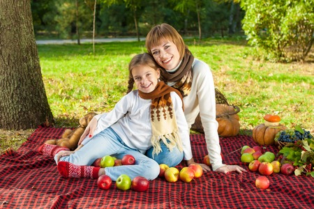 Beautiful mother and daughter sitting at a picnic on a sunny day. With apples. Autumn. photo