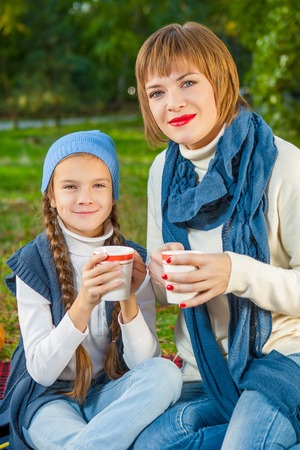 beautiful happy mother and daughter sitting on a picnic. With a cup of hot tea. photo