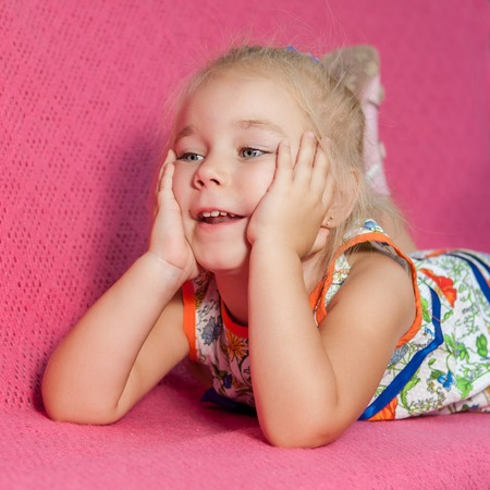 capricious: Adorable little girl lying on pink  background. Capricious, cheerful.