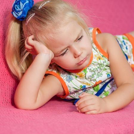 fantasque: Adorable petite fille couch�e sur fond rose. Capricieuse, triste.